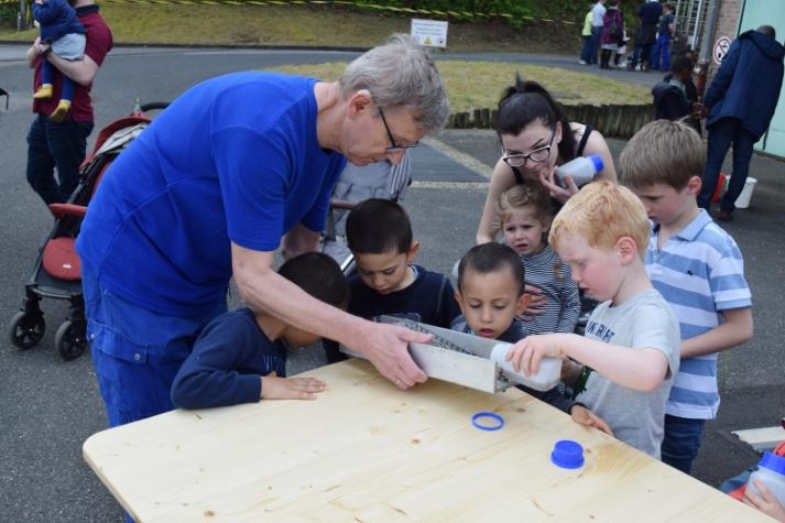 Kinder gießen Abwasser durch ein kleines Rechenmodell und lernen so, dass Grobstoffe zurückgehalten werden.